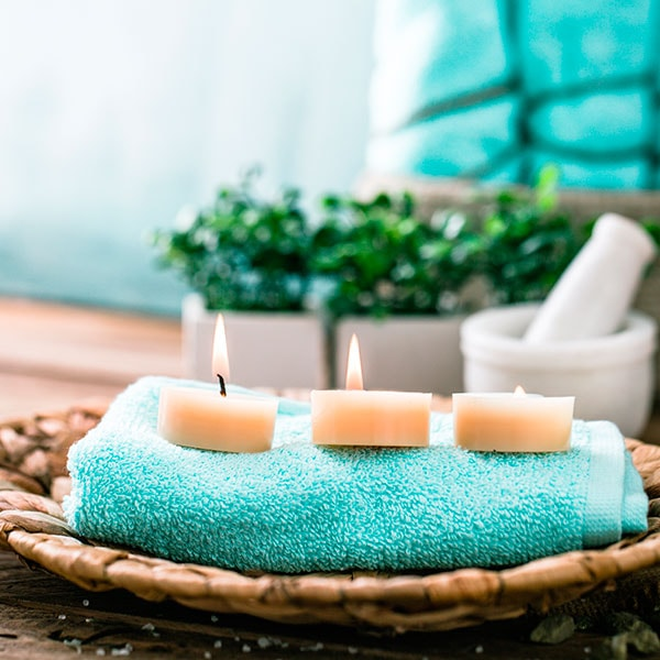 Three candles on top of a spa towel