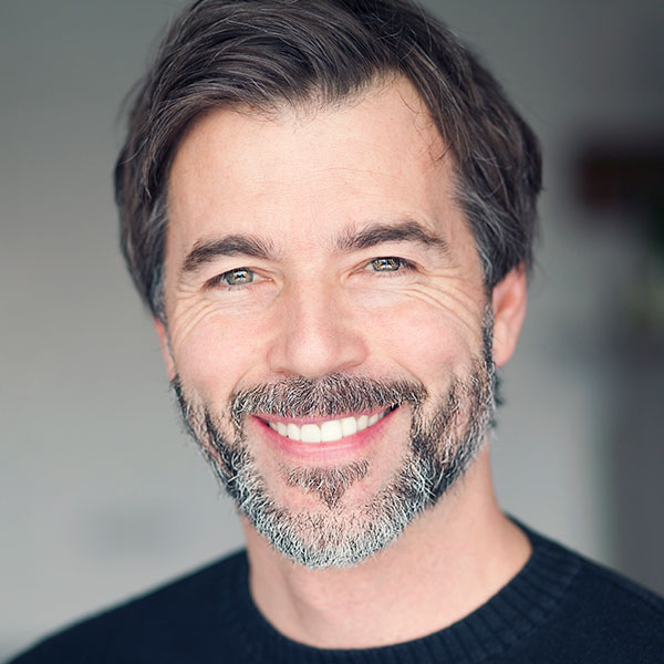 A mature man with a beard smiling with his new dental implants
