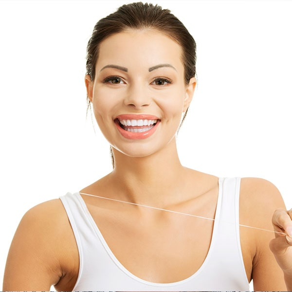 A young woman taking care of her porcelain veneers by flossing