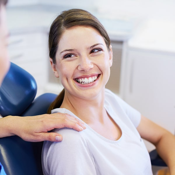 A young woman looking up at her dental hygienist from the dental chair