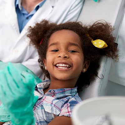 A little girl at the dentist smiling while playing with the doctors' gloves