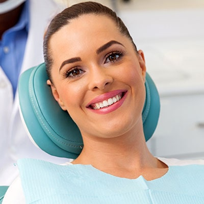 A young woman smiling in a dental chair