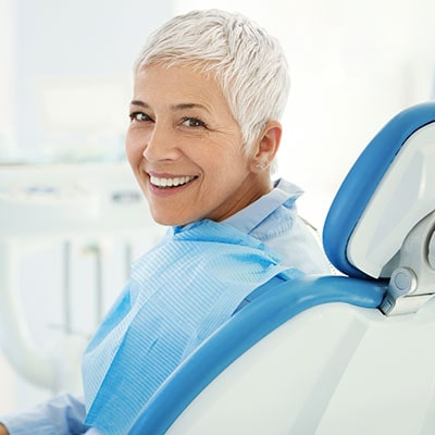 A mature woman smiling in a dental chair