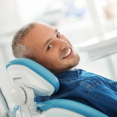 A mature man reclining in a dental chair