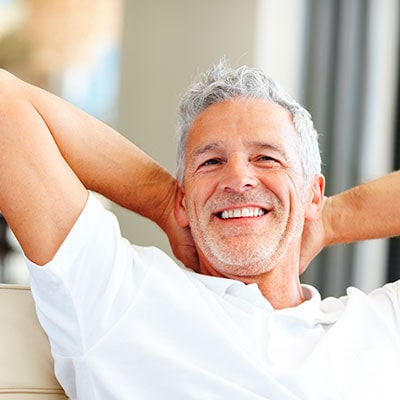A man with dentures smiling while sitting on a sofa