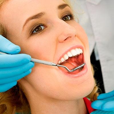 The dentist checking a woman's teeth