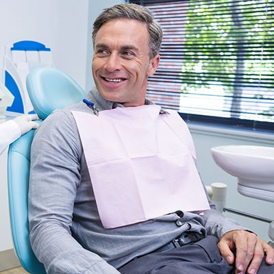 An older man looking at his dentist from the dental chair