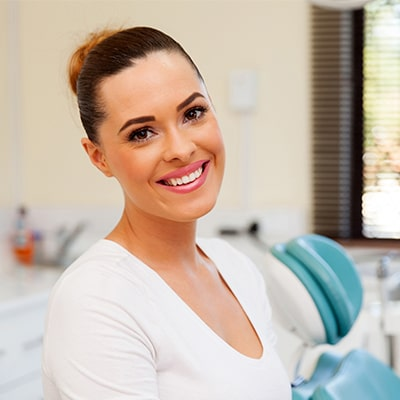 A woman at the dentist standing smiling