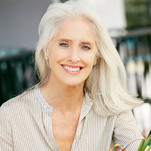 A mature white haired woman smiling outside