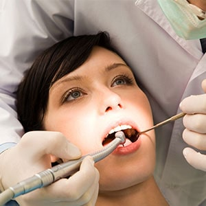 A dentist using a dental drill on a female patient's mouth