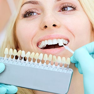 The dentist checking the color tone of a woman's teeth