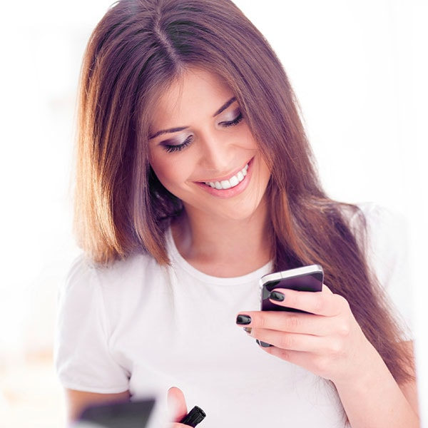 A red-haired woman with white teeth looking at her cell phone while smiling